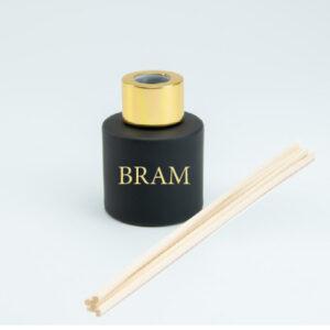 Rond mat zwart parfumflesje met gouden sluiting en geurstokjes